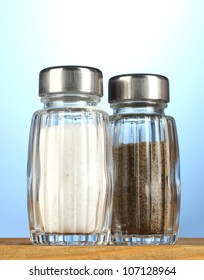 Salt and pepper mills, on wooden table on blue background