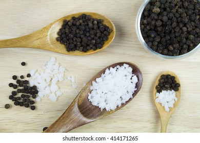 salt and pepper on wooden spoons
