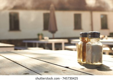 Salt and Pepper shakers on an empty wooden table in an empty outdoors cafe - copy space