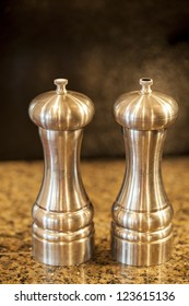 Salt and pepper shakers on a granite counter top.