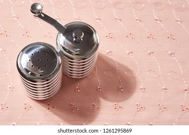 salt and pepper shakers on the pink table cloth