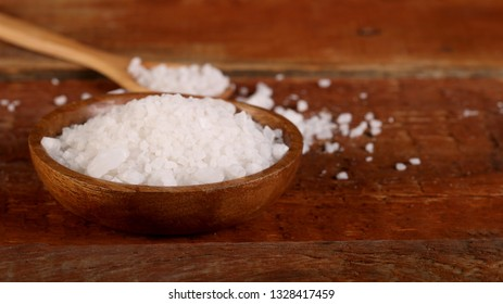 Salt or sea salt in a wooden bowl on a aged wooden table background.