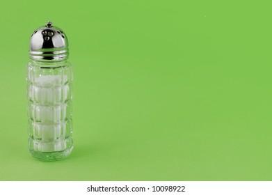 Salt shaker on green background