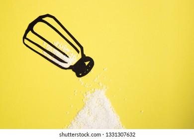Salt shaker paper cutout adding salt to a pile of salt on bright yellow background