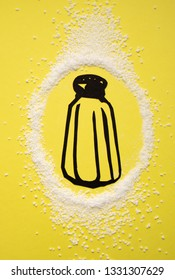 Salt shaker paper cutout in a circle of salt on bright yellow background
