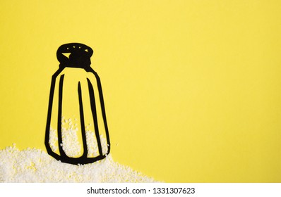 Salt shaker paper cutout standing on a pile of salt on a bright yellow background