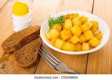 Salt shaker, slices of bread, white plate with cubes of fried potatoes, fork on wooden table