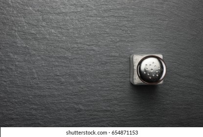 salt shaker with white salt on black stone background, top view