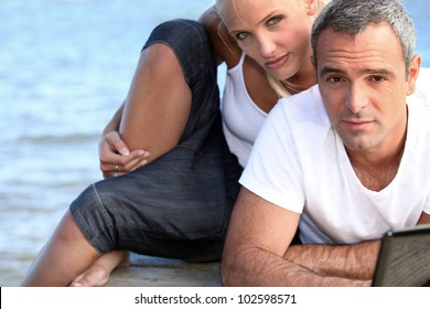 salt-and-pepper guy with laptop posing with younger girlfriend
