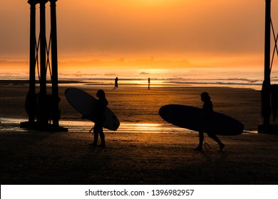 Saltburn, Cleveland / England May 13th 2019 : Saltburn pier at sunset.  This pier has just recently celebrated its 150th year. Two surfers returning from the sea.