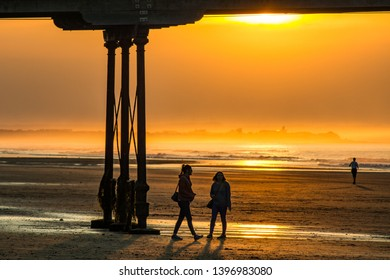 Saltburn, Cleveland / England May 13th 2019 : Saltburn pier at sunset.  This pier has just recently celebrated its 150th year. Two people walking under the pier.