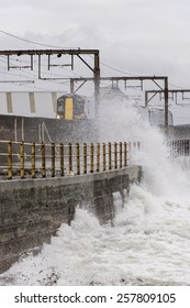 SALTCOATS, SCOTLAND - APRIL 14, 2013: A Train passing through Saltcoats travels next to the coastline as waves crash over the sea wall