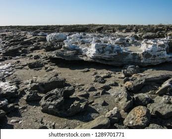 Salt-covered cliff in Kara-Bogaz-Gol Bay, and flying salty foam from the bay. The Karakum, Turkmenistan.