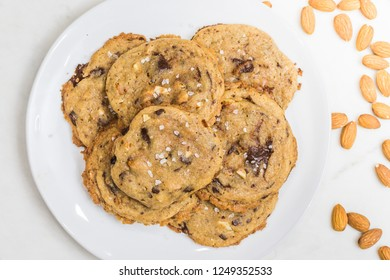 Salted brown butter, chopped almond and dark chocolate cookies recipe. Top view. Soft, gooey, fresh out of the oven delicious desserts, pastries, sweets, treats.