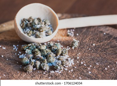 Salted capers of a wooden chop board, macro details of capers, salt and wooden spoon