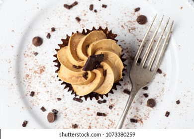Salted Caramel cupcake on white plate with fork, dusted with cocoa powder and chocolate sprinkles, Overhead View