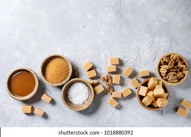 Salted caramel fudge candy served with fleur de sel, caramel sauce, brown cane sugar and caramelized walnuts in wooden bowls over grey texture background. Top view, space. Dessert set