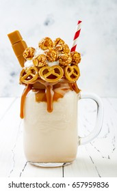 Salted caramel indulgent extreme milkshakes with brezel waffles, popcorn and whipped cream. Crazy freakshake food trend.