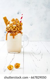 Salted caramel indulgent extreme milkshakes with brezel waffles, popcorn and whipped cream. Crazy freakshake food trend. Copy space