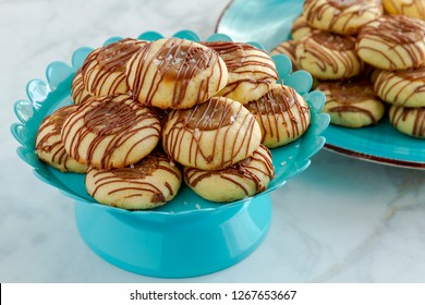 Salted caramel thumbprint cookies drizzled with milk chocolate sitting on bright blue pastry and blue plate of additional cookies in background