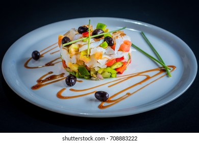 Salted cod (bacalao) dish, on a white plate and dark background.