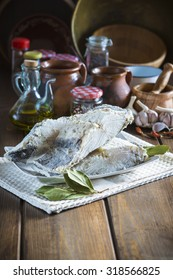 Salted cod cut with ingredients and utensils on the table of the kitchen for cooking