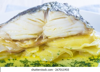 Salted cod fish oven baked with potatoes onion and olive oil