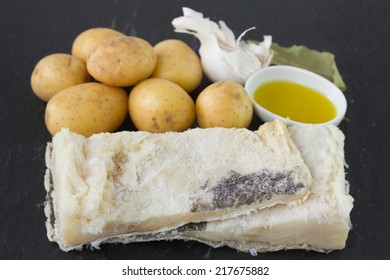 salted cod fish with potato, olive oil and garlic on black background