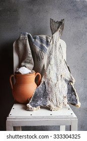 Salted cod fish and a rustic clay pot with sea salt  on a white chair