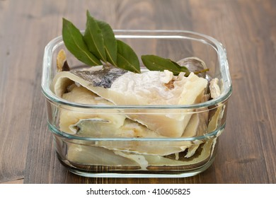 salted cod fish in water in glass dish on brown background