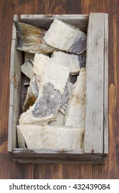 salted cod fish in wooden box on brown background
