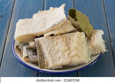 salted codfish on dish on blue wooden background