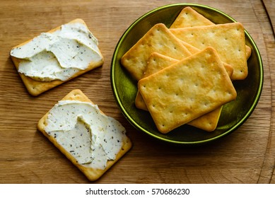 Salted crackers with herbal cream cheese on wooden tray. A tasty and humble snack.