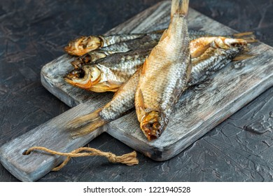 Salted dried river fish on wooden serving board on dark background, selective focus.