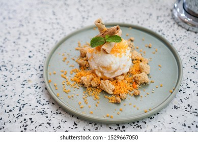 Salted Egg ice cream. A plate of salted egg ice cream scoop topped with crispy roll, crumble cookies and salted egg sliced.