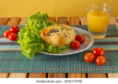Salted with hamburger meat, gergilim, lettuce and tomatoes. Orange juice. Wooden table and porcelain dish.