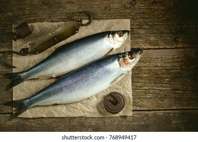 Salted herring fish on an old wooden background with antique hand weights. Rustic style.