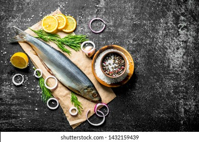 Salted herring on paper with spices, onions and lemon. On dark rustic background
