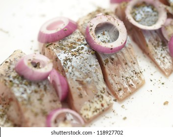 salted herring on the plate with red onion
