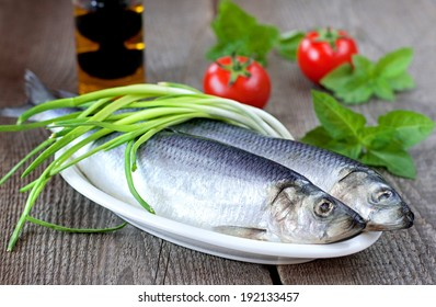 Salted herring on a wooden table with green onion, tomatoes, green basil and olive oil