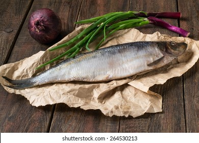 Salted herring, red and green onions on wrapping paper and wooden background. Selective focus