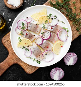 Salted herring with spices, lemon and red  onion rings on black stone background . Marinated sliced fish. top view