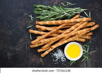 Salted italian breadsticks with rosemary and salt. Above view with space on a dark brown stone background