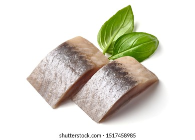 Salted marinated Atlantic herring with fresh green basil, isolated on white background.