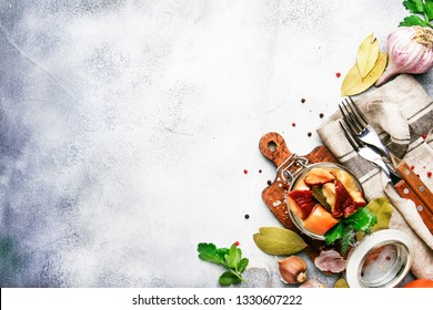 Salted or marinated white mushrooms in glass jar with spices and herbs, cooking food canning concept, gray kitchen table background, place for text, top view