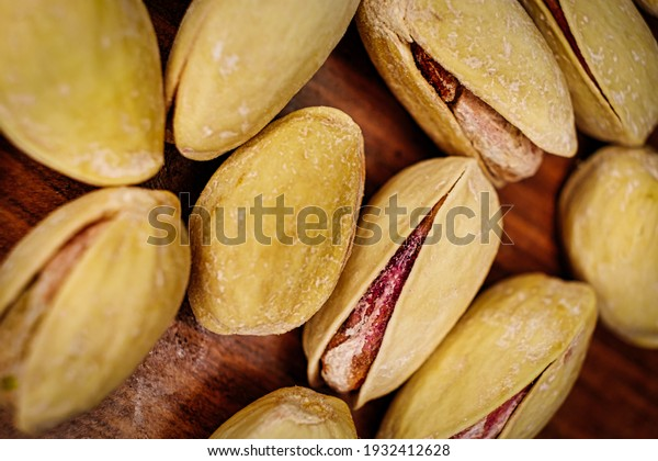 Salted pistachio pistache nuts macro image. A lot of salty pistachios lies on a wooden background with open shells