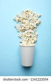 Salted popcorn and a disposable glass on a blue pastel background. Top view.