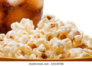 Salted popcorn grains in the dish and a glass of cola on the white background