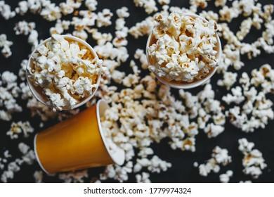 Salted popcorn in orange paper cups, on black background