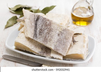 salted raw dry cod fish on dish and olive oil